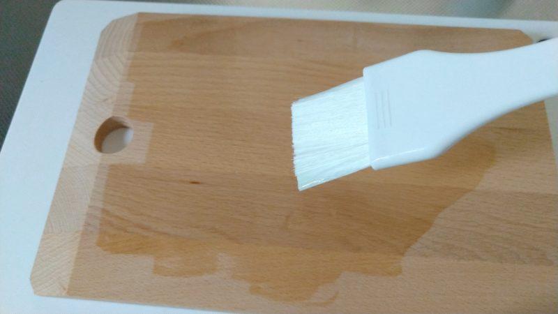 木のまな板にハケでアマニ油を塗る